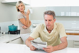 Man reading newspaper while woman at kitchen