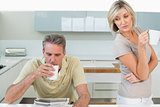 Couple with coffee cups reading newspaper in kitchen