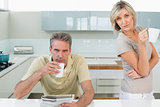 Serious couple with coffee cups and newspaper in kitchen