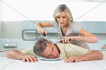Angry woman holding knife to man's neck in kitchen