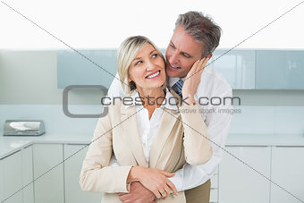 Man embracing happy woman from behind in kitchen
