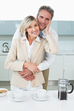 Man embracing a happy woman from behind in kitchen