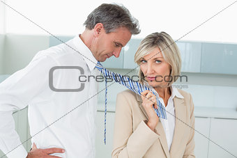 Woman holding a man by his neck tie in kitchen