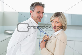 Woman holding a happy man by his tie in kitchen