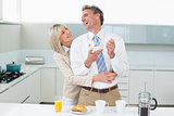 Woman embracing a happy man from behind in kitchen