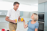 Happy couple with orange juices in kitchen