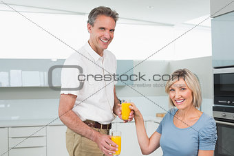 Couple with orange juices having breakfast in kitchen