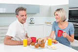 Happy couple having breakfast in kitchen