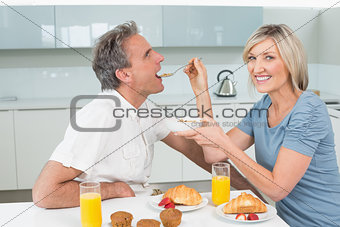 Woman feeding man at breakfast table in kitchen