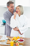 Man embracing a woman from behind in kitchen