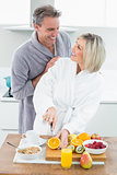 Man with a woman as she cuts fruits in kitchen