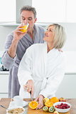 Man drinking orange juice and woman cutting fruits in  kitchen