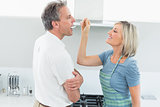 Happy woman feeding man in the kitchen