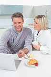 Couple in bathrobes using laptop in kitchen