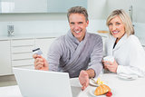 Couple doing online shopping in kitchen