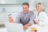 Couple in bathrobes doing online shopping in kitchen