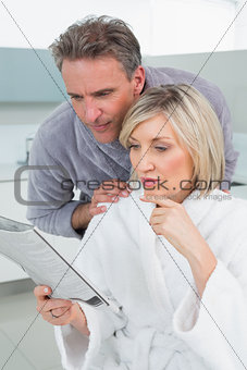Serious couple in bathrobes reading newspaper