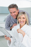 Happy couple in bathrobes with newspaper in kitchen