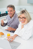 Couple in bathrobes with coffee and juice using laptop in kitchen
