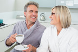 Happy loving couple with coffee cup in kitchen