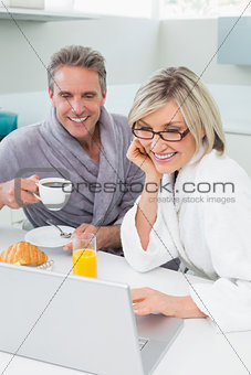 Couple in bathrobes with coffee and juice using laptop