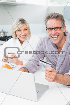 Cheerful couple in bathrobes using laptop in kitchen