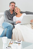 Couple using laptop in the living room