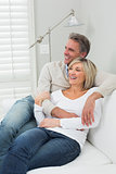 Happy loving couple embracing on sofa at home