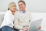 Happy casual couple using laptop in at home