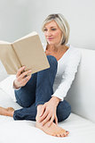 Relaxed woman reading book at home