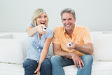 Cheerful couple with remote controls in a house