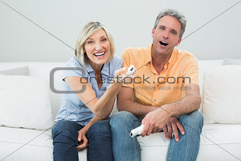 Portrait of a cheerful couple with remote controls