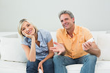 Portrait of a relaxed happy couple with remote controls