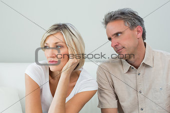 Displeased couple sitting on sofa after a fight