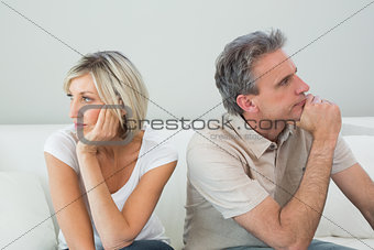Relaxed couple sitting on sofa after a fight