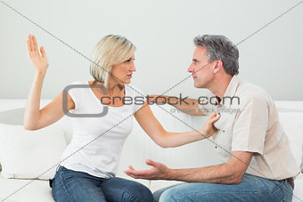 Angry woman about to slap a man at home