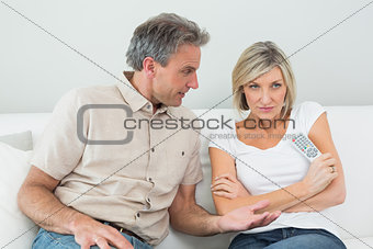 Serious couple watching tv at home