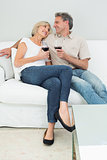Relaxed couple with wine glasses at home