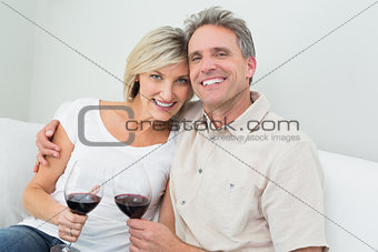 Happy couple with wine glasses at home