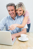 Casual couple using laptop at home