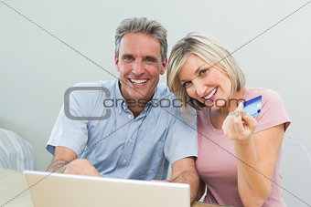 Cheerful couple doing online shopping at home