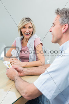 Cheerful couple playing cards at home