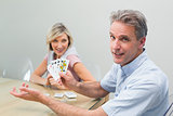 Happy man and woman playing cards at home