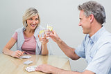 Couple toasting lime juices while playing cards at home