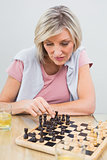 Concentrated woman playing chess at table