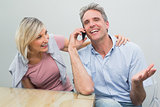 Happy casual couple using mobile phone