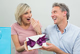 Man giving a surprised woman a birthday gift