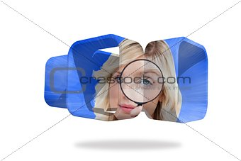 Blonde holding magnifying glass on abstract screen