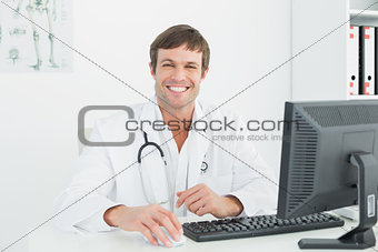 Smiling male doctor with computer at medical office