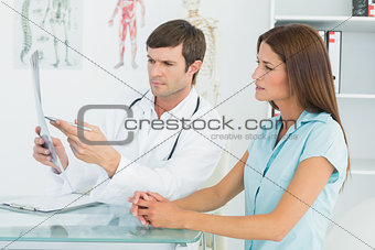 Male doctor explaining lungs x-ray to female patient
